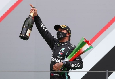 Formula One F1 - Portuguese Grand Prix - Algarve International Circuit, Portimao, Portugal - October 25, 2020 Mercedes' Lewis Hamilton celebrates winning the race with the trrophy on the podium
