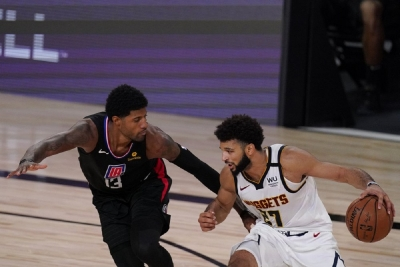 Denver Nuggets' Jamal Murray (27) drives past Los Angeles Clippers' Paul George (13) during the second half of an NBA conference semifinal playoff basketball game Saturday, Sept. 5, 2020, in Lake Buena Vista, Fla.