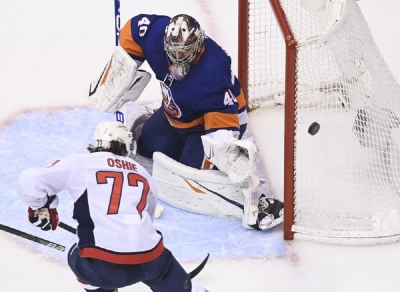 New York Islanders goaltender Semyon Varlamov (40) makes a save against Washington Capitals right wing T.J. Oshie (77) during third period NHL Eastern Conference Stanley Cup playoff hockey action in Toronto on Tuesday, Aug. 18, 2020.