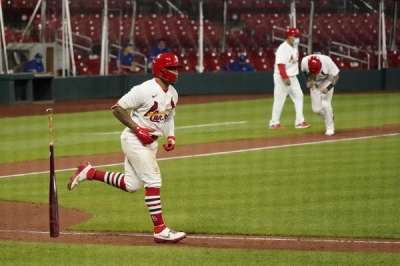 St. Louis Cardinals' Kolten Wong, left, tosses his bat after earning a bases loaded walk allowing Yadier Molina, right, to score the game-winning run during the ninth inning of a baseball game against the Kansas City Royals Wednesday, Aug. 26, 2020, in St. Louis.