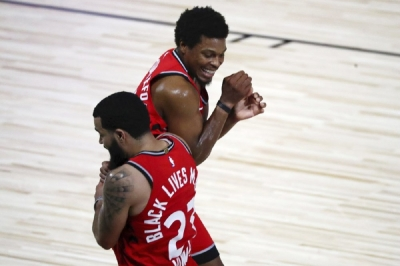 Toronto Raptors guard Fred VanVleet (23) celebrates with guard Kyle Lowry (7) after making a half court shot against the Brooklyn Nets to end the first half in Game 3 of an NBA basketball first-round playoff series, Friday, Aug. 21, 2020, in Lake Buena Vista, Fla.
