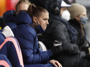 In this file photo dated Saturday, Oct. 10 2020, Tottenham Hotspur's Alex Morgan sits in the stands during the English Women's Super League soccer match against Manchester United at the Hive stadium in London. The American World Cup winner Alex Morgan said Thursday Oct. 29, 2020, that she hopes to make her Tottenham debut within two weeks, as she is still regaining match fitness after giving birth in May