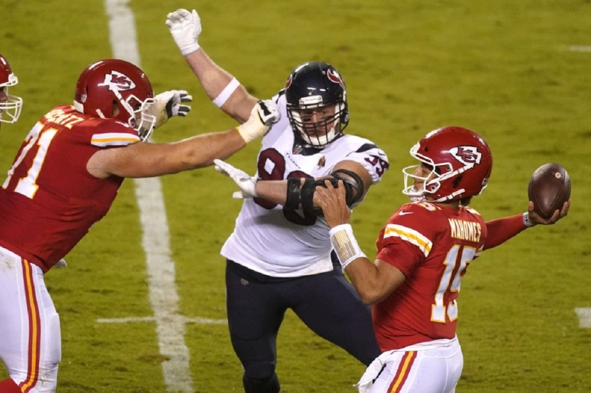Kansas City Chiefs quarterback Patrick Mahomes (15) passes as he is pressured by Houston Texans defensive end J.J. Watt (99) in the first half of an NFL football game Thursday, Sept. 10, 2020, in Kansas City, Mo
