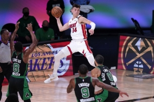 Miami Heat guard Tyler Herro (14) leaps to make a pass over Boston Celtics' Kemba Walker (8), Brad Wanamaker (9) and Jayson Tatum (0) during the second half of an NBA conference final playoff basketball game, Thursday, Sept. 17, 2020, in Lake Buena Vista, Fla.