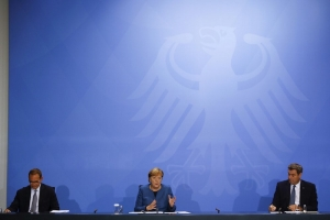 German Chancellor Angela Merkel (CDU), Bavarian Prime Minister Markus Soeder (CSU), right, and Berlin's Mayor Michael Mueller (SPD) hold a press conference at the Chancellery in Berlin, Wednesday, Oct. 28, 2020. Merkel is pressing for a partial lockdown as the number of newly recorded infections in the country hit another record high Wednesday