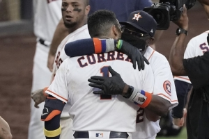 Houston Astros Carlos Correa is hugged by Houston Astros manager Dusty Baker Jr. after his walk off home run during the ninth inning in Game 5 of a baseball American League Championship Series, Tuesday, Dec. 15, 2020, in San Diego. The Astros defeated the Rays 4-3 and the Rays lead the series 3-2 games.