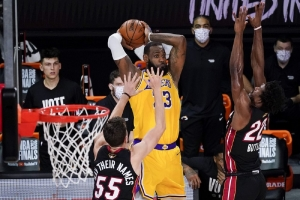 Los Angeles Lakers forward LeBron James passes between Miami Heat guard Duncan Robinson, left, and forward Jimmy Butler during the second half in Game 4 of basketball's NBA Finals Tuesday, Oct. 6, 2020, in Lake Buena Vista, Fla.