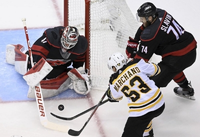 Carolina Hurricanes goaltender James Reimer (47) makes a save on a shot from Boston Bruins left wing Brad Marchand (63) as Hurricanes defenseman Jaccob Slavin (74) looks on during first-period NHL Eastern Conference Stanley Cup playoff hockey action in Toronto, Monday, Aug. 17, 2020.