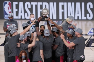 The Miami Heat celebrate their NBA conference final playoff basketball game win over the Boston Celtics with the Eastern Final trophy Sunday, Sept. 27, 2020, in Lake Buena Vista, Fla.