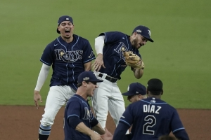 Tampa Bay Rays' Willy Adames, back left, and Brandon Lowe celebrate after the Rays defeated the New York Yankees 2-1 in Game 5 of a baseball AL Division Series, Friday, Oct. 9, 2020, in San Diego
