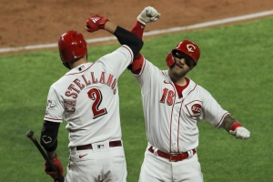 Cincinnati Reds' Nick Castellanos, left, and Tucker Barnhart celebrates Barnhart's solo home run during the third inning of the team's baseball game against the Chicago White Sox in Cincinnati, Friday, Sept. 18, 2020.