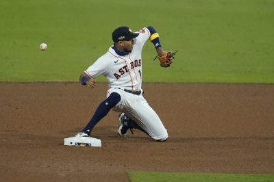 Houston Astros shortstop Carlos Correa misses a throw from Houston Astros' Jose Altuve as Tampa Bay Rays Randy Arozarena is safe at second on a hit by Brandon Lowe during the sixth inning in Game 3 of a baseball American League Championship Series, Tuesday, Oct. 13, 2020, in San Diego.